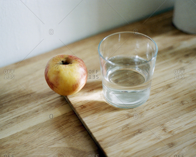 Still life with apple and water glass on wooden board