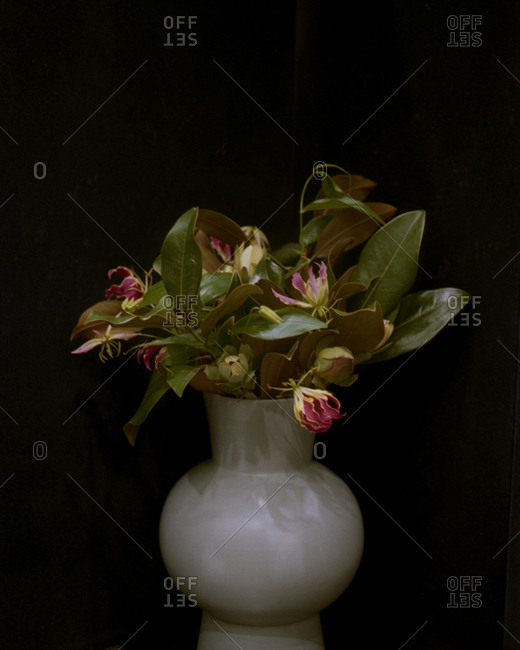 White vase with bouquet of wilted flowers