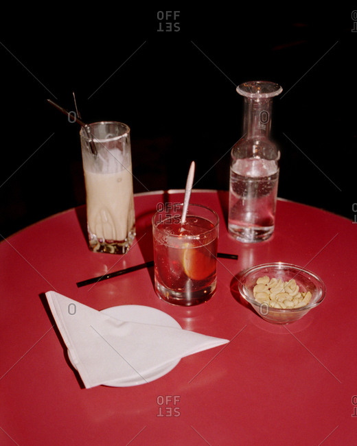 Mixed drinks served on table with bowl of peanuts