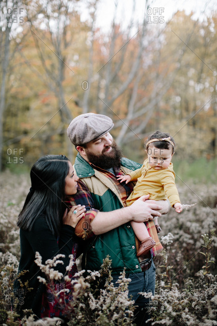 Father holding baby girl while family is taking a nature walk