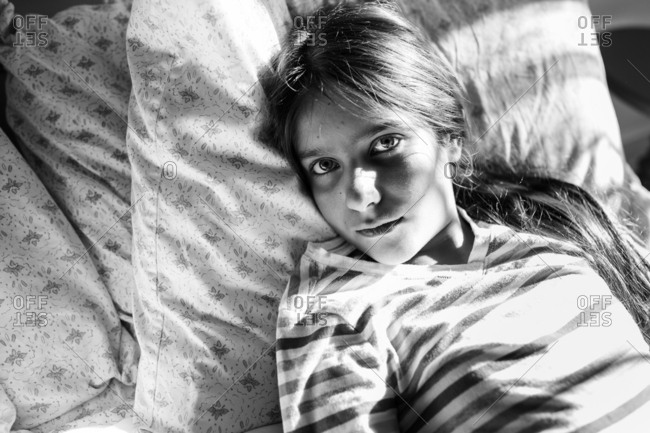 Pre-teen girl relaxing in bed in black and white