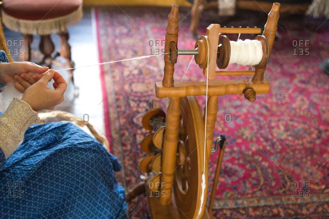Girl spinning wool into yarn