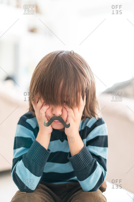 Boy with a fake mustache resting his chin in his hands