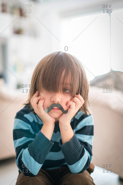 Little boy with a fake mustache looking worried