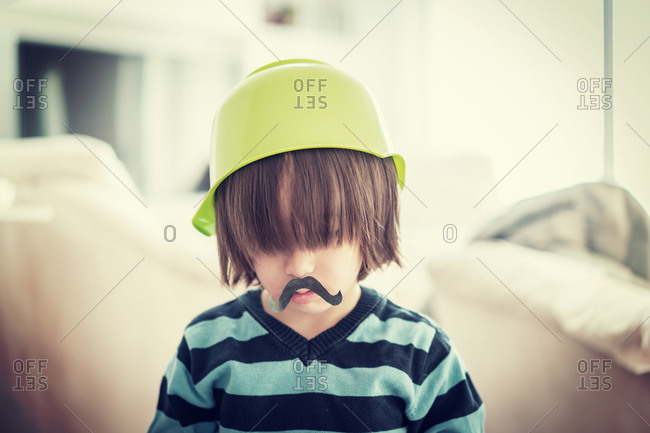 Little boy with a paper mustache and a bowl on his head