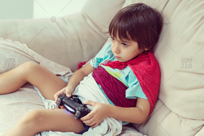 Boy wrapped in a blanket playing a video game