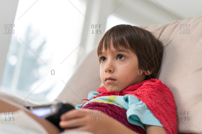 Boy sitting on a couch playing a video game