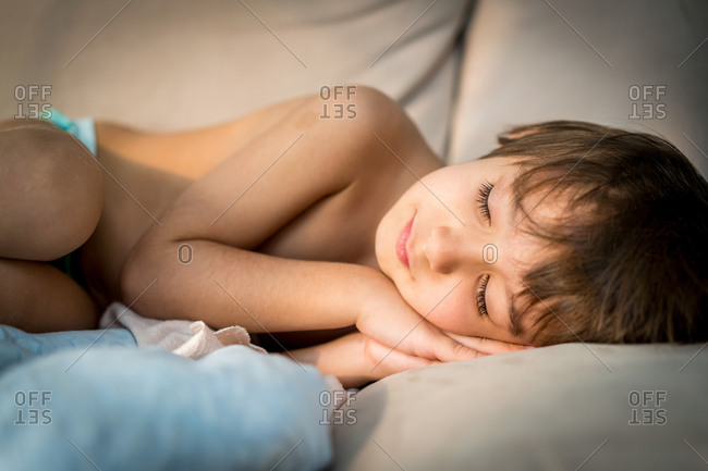 Child curled up sleeping on a couch