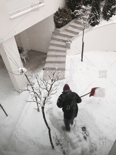 a man is cleaning snow from his house