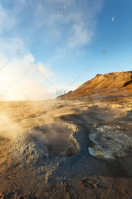Sunlit mist rising from the Hverir Hot springs on Namafjall with the moon in the blue sky, Northeast Iceland