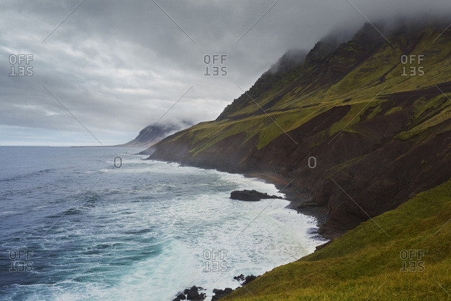 Fog over the cliffs of the Icelandic coast and the Atlantic Ocean in Northeast Iceland