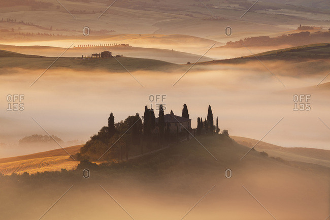Overview of Podere Belvedere in a sunlit mist at sunrise at San Quirico D'Orcia in Val d'Orcia in Tuscany, Italy