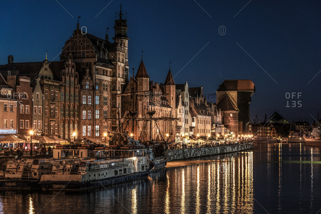 Gdansk, Poland - August 30, 2016: Motlawa river with The Crane and St. Mary's Gate at night