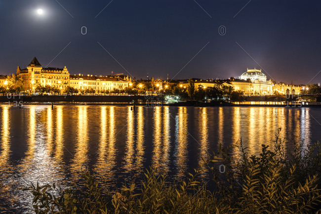 Czech Republic- Prague- view to National theatre with Vltava in the foreground at night