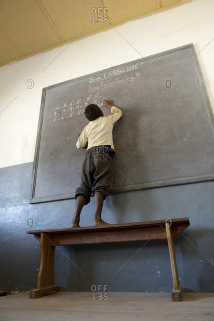 Madagascar- Fianarantsoa- Schoolboy writing on blackboard