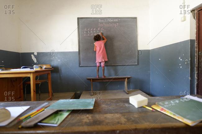 Madagascar- Fianarantsoa- Schoolgirl writing on blackboard