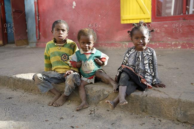 Madagascar- Fianarantsoa- Homeless children sitting on pavement