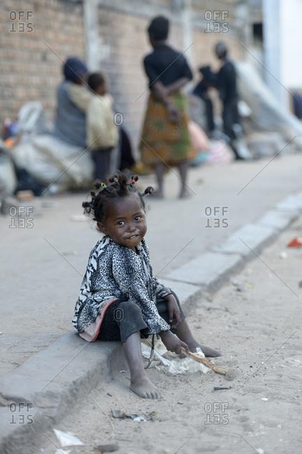 Madagascar- Fianarantsoa- Homeless girl sitting on pavement