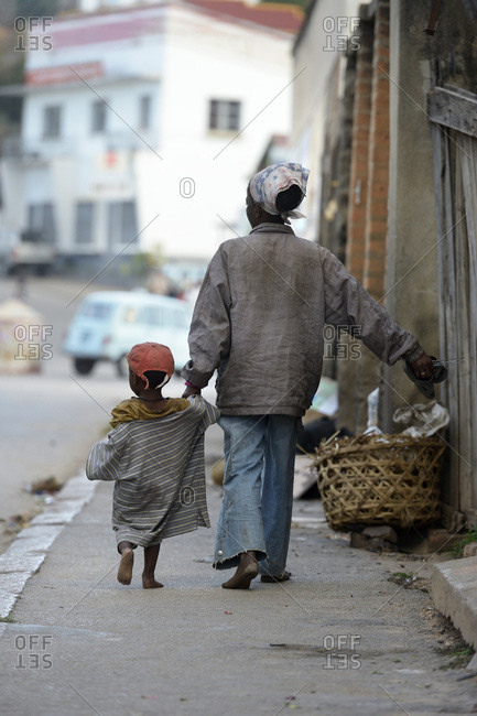 Madagascar- Fianarantsoa- Homeless mother with her child walking in the street