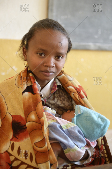 Madagascar- Fianarantsoa- Young mother holding baby in her arms