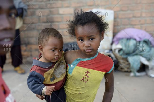 Madagascar- Fianarantsoa- Homeless little girl carrying toddler