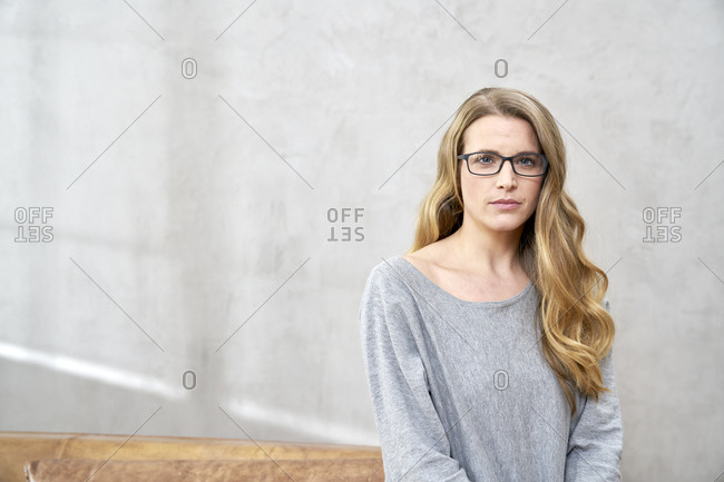 Portrait of serious blond woman wearing glasses