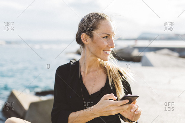 Smiling young woman with cell phone at the seafront  looking around