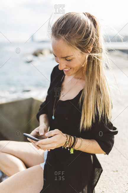 Smiling young woman at the seafront using cell phone