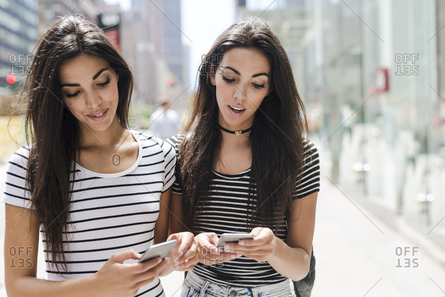 USA- New York City- two twin sisters looking at cell phones in Manhattan