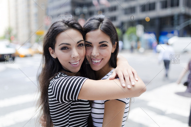 USA- New York City- portrait of two beautiful twin sisters in Manhattan hugging