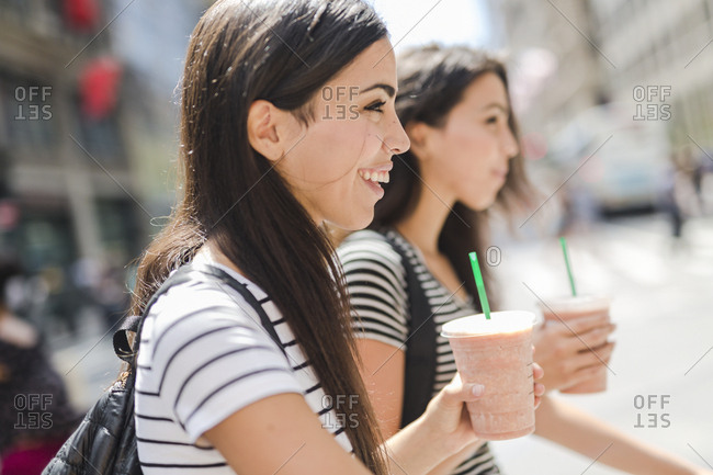 USA- New York City- two happy twin sisters on the go in Manhattan with takeaway drink
