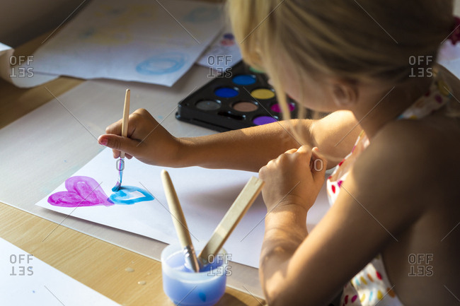 Little girl painting hearts with watercolors