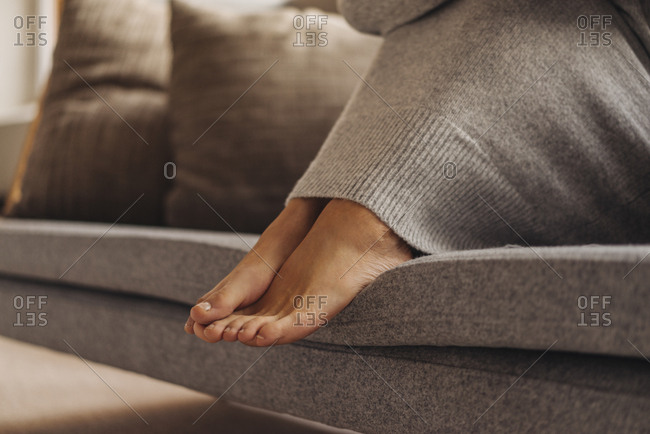 Close-up of woman's feet sitting on couch