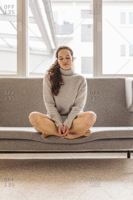 Woman with closed eyes sitting on couch