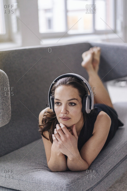 Woman lying on couch wearing headphones