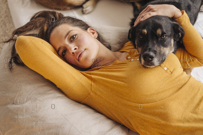 Woman lying in bed with her dog
