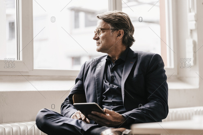 Mature businessman holding tablet looking out of window
