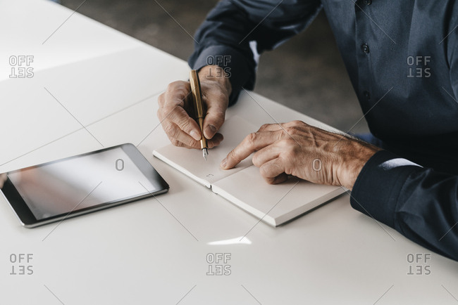 Businessman writing in notebook next to tablet