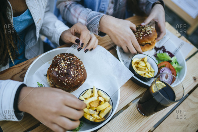Women's hands eating Hamburgers and French fries