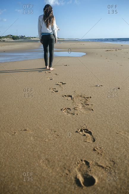 Back view of young woman walking on the beach leaving her footprints in the sand
