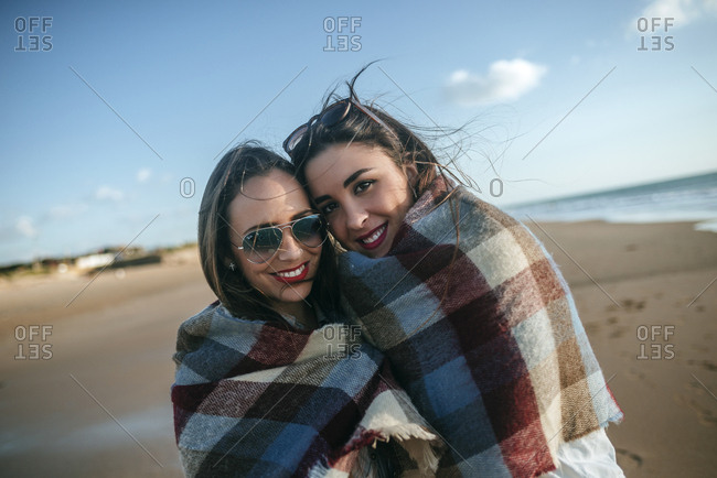 Portrait of two women covered with blanket on the beach