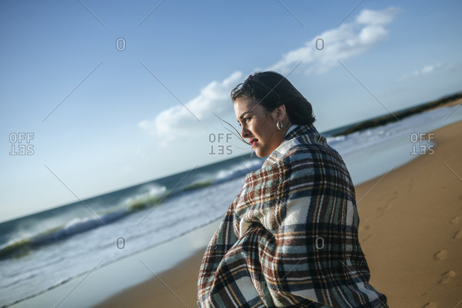 Young woman with blanket on the beach looking at the se