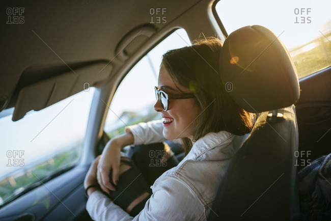 Young woman with sunglasses in car at evening twilight