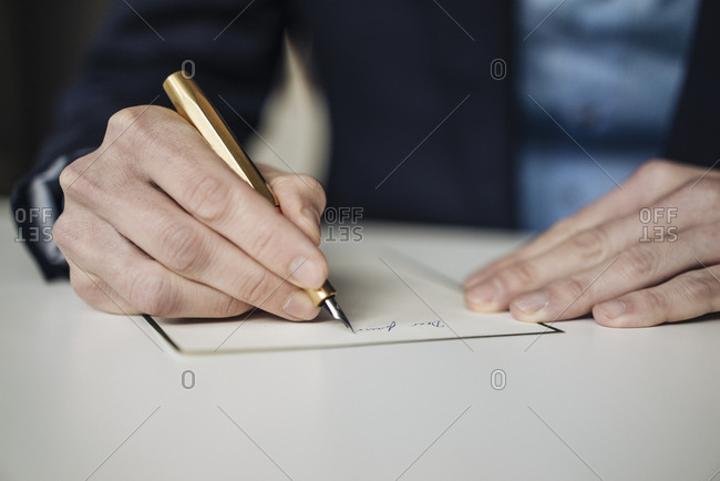Hand of businessman writing with golden fountain pen