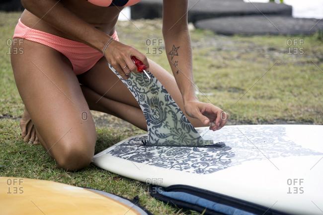 Woman preparing surfboard on meadow