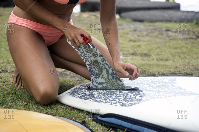 Woman preparing surfboard on meadow
