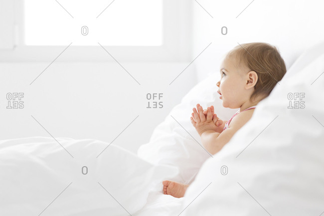 Baby girl sitting between pillows on a white bed