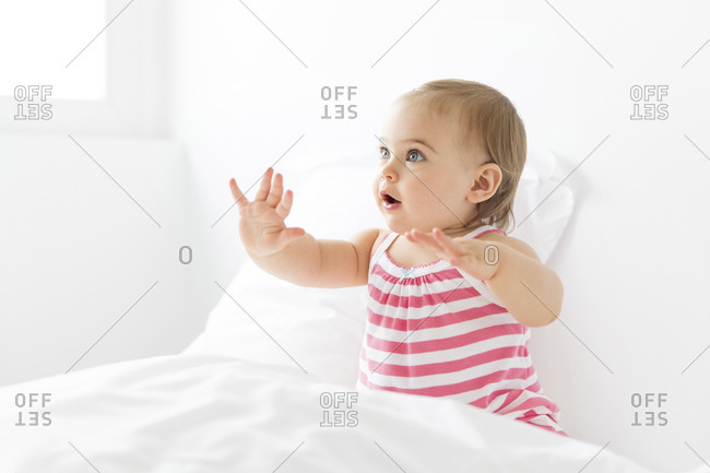 Baby girl sitting on a white bed waving her hands