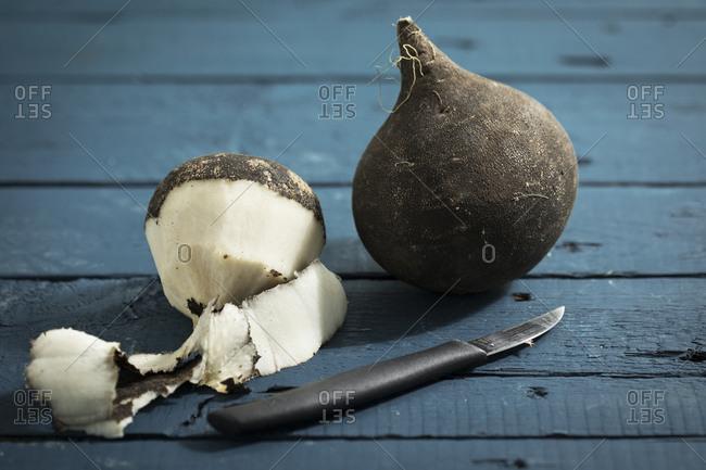 Whole and peeled black radish and a kitchen knife
