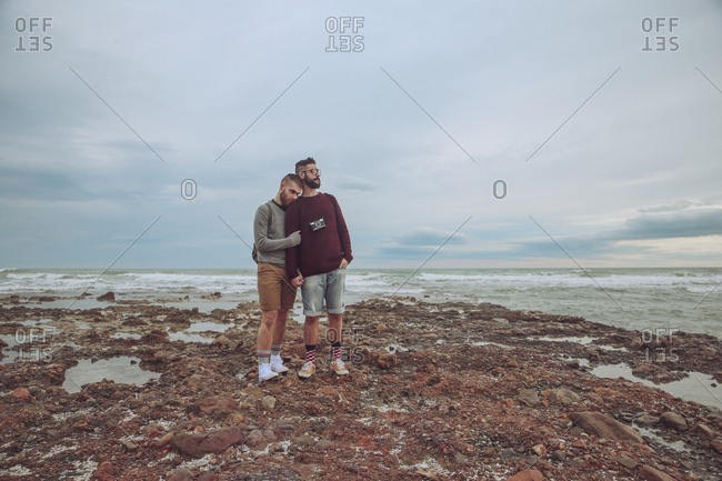 Young gay couple standing hand in hand on the beach